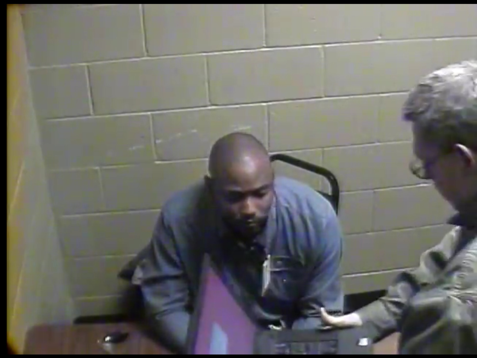 Sgt. James Young (right) brought in a laptop to show Michael Cunningham the surveillance video of what happened outside the convenience store. Young and fellow officer Haber. now the Balch Springs chief, said the video did not show an assault. A federal judge disagrees.