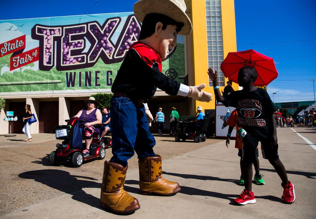 Big Little Tex gets a high-five from Benjamin Smith, 8, at the State Fair of Texas on Oct. 4, 2017 at Fair Park in Dallas. (Ashley Landis/The Dallas Morning News)