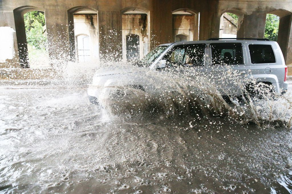 A car drives through standing water at 2400 Sylvan Ave., in Dallas on Sept. 22, 2018. (Carly Geraci/The Dallas Morning News)