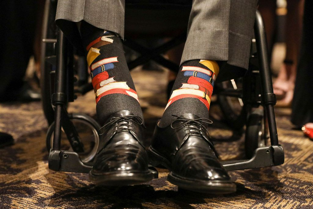 This Saturday, April 21, 2018, photo provided by the office of former U.S. President George H.W. Bush shows Bush's socks decorated with books. He wore them during the funeral service for his wife, Barbara Bush, in Houston.  Barbara Bush was known for bringing awareness to AIDS patients and for her work promoting literacy, which her husband subtly honored Saturday by wearing socks printed with blue, red and yellow books. (Paul Morse/Courtesy of Office of George H.W. Bush via AP)