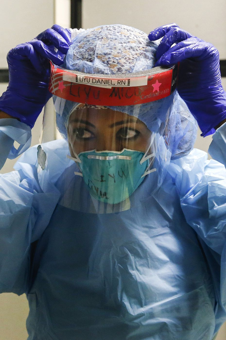 Nurse Liyu Daniel dons personal protective equipment as she prepares to enter the COVID-19 Tactical Care Unit at Parkland Memorial Hospital.