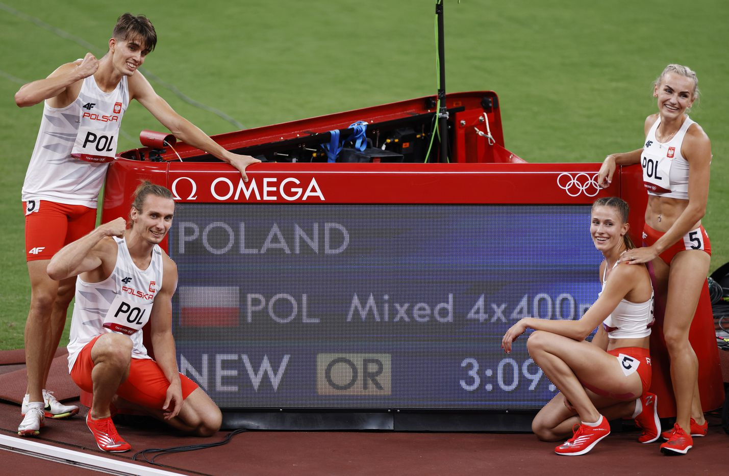 (From l to r) Poland's Kajetan Duszynski, Karol Zalewski, Natalia Kacmarek and Justyna Swiety-Ersetic pose with the scoreboard displaying their new Olympic record after winning the mixed 4x400m relay final during the postponed 2020 Tokyo Olympics at Olympic Stadium, on Saturday, July 31, 2021, in Tokyo, Japan. (Vernon Bryant/The Dallas Morning News)