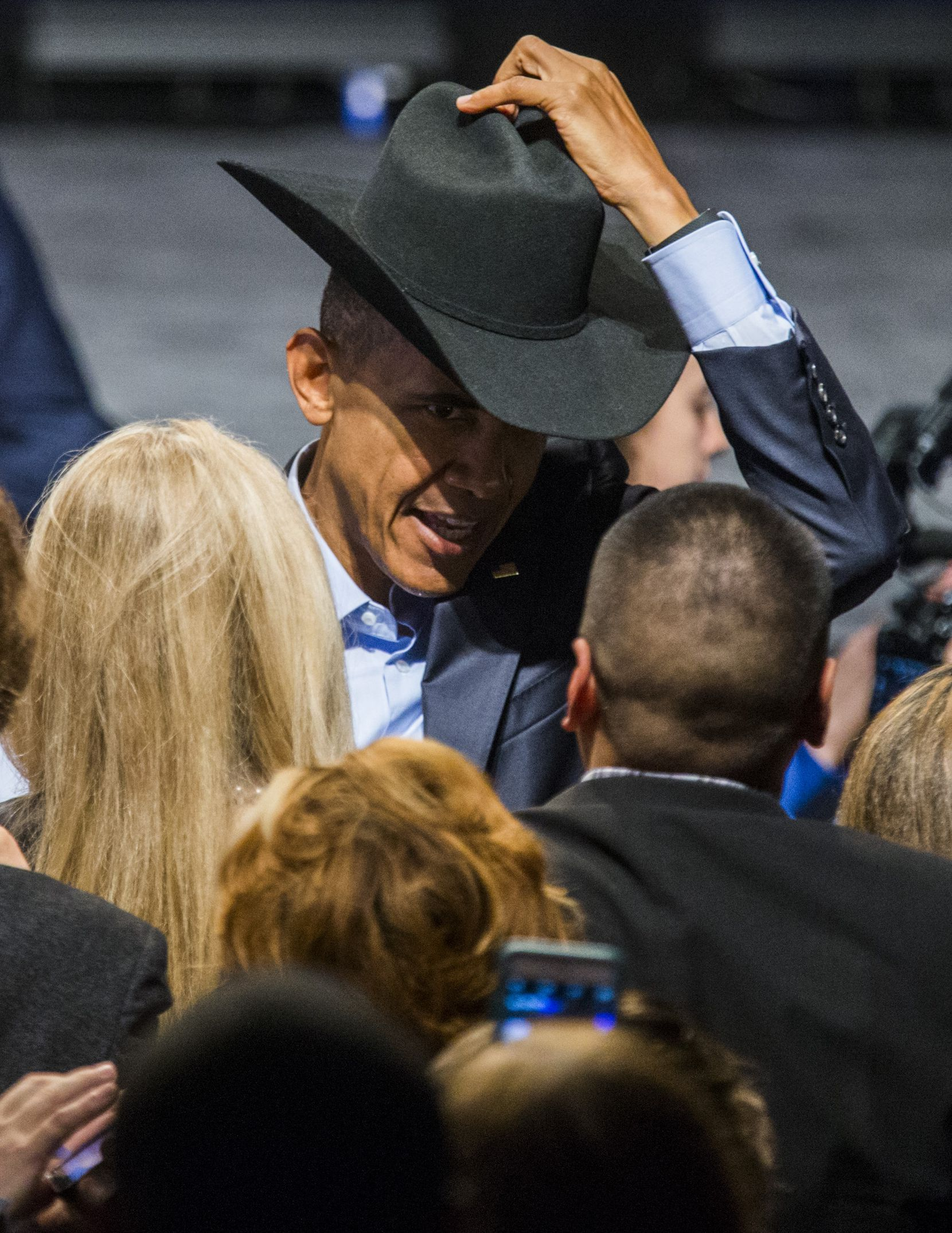 President Barack Obama tries on a cowboy hat from a member of the crowd after speaking at a Democratic National Committee event at Gilley's Club Dallas on March 12, 2016, in Dallas.