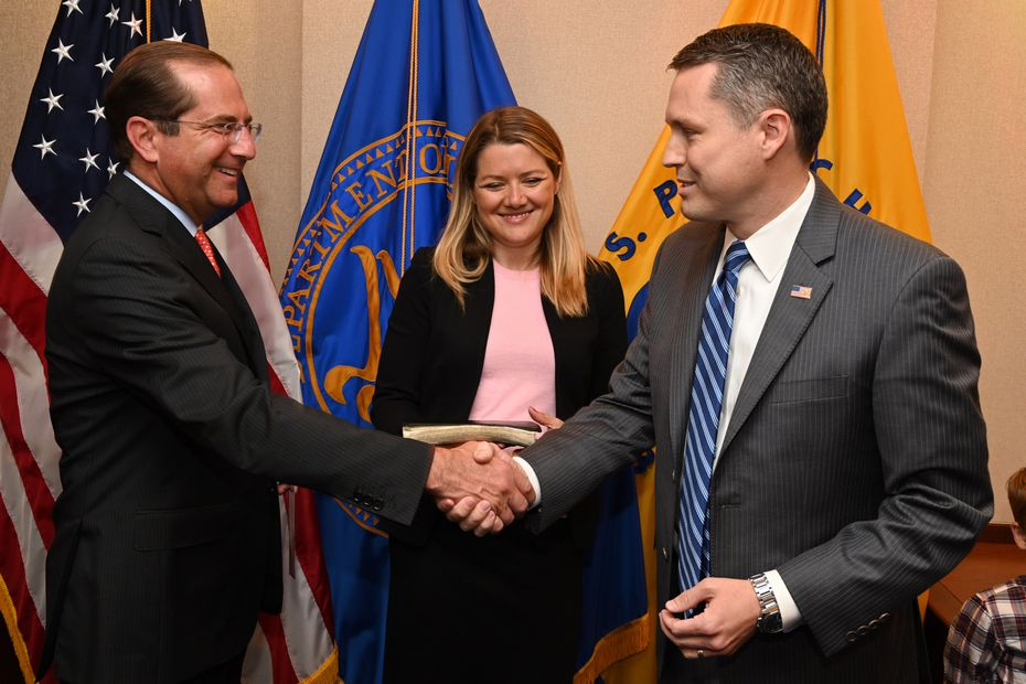 Alex Azar (left) U.S. Secretary of Health and Human Services, congratulates Brian Harrison as his wife, Tara Napier Harrison, looks on after Harrison's swearing-in on June 17, 2019, as chief of staff at the department. Photo by official HHS photographer Chris Smith.