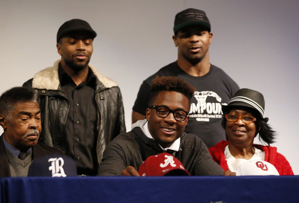 Sachse defensive back Jared Mayden picks up an Alabama hat signaling his intent to play football for Alabama during a signing day ceremony at Sachse High School in Sachse on Wednesday, February 3, 2016. Mayden's grandfather Donald Pierson (left), cousins Marquise Pierson (top left), Marquale Pierson (top right) and grandmother Alberta Pierson join him on the stage during his selection. (Vernon Bryant/The Dallas Morning News)