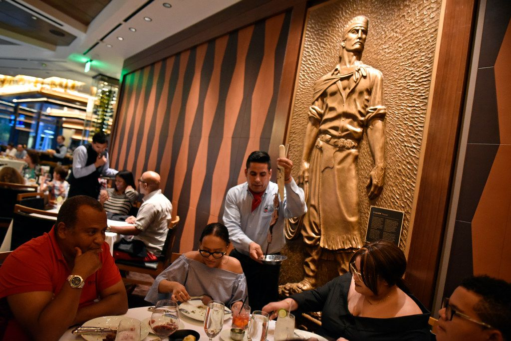 A brass gaucho is on display inside the main dinning hall as Eduardo Rodriguez serves meat to the de sa Santos family  inside the new Fogo de Ch‹o in Uptown, Friday, May 19, 2017 in Dallas. Ben Torres/Special Contributor