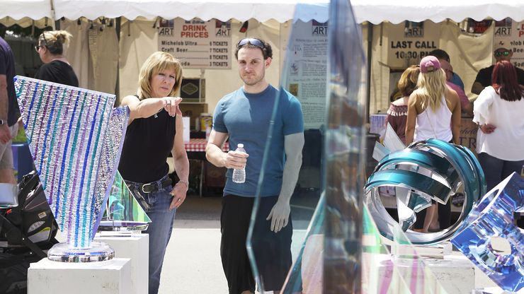 Christine Riggs and Brandon Allen browse through the works of visual artists at the 2018 Art in the Square in Southlake. The 2021 event takes place Sept. 24-26 at Southlake Town Square.