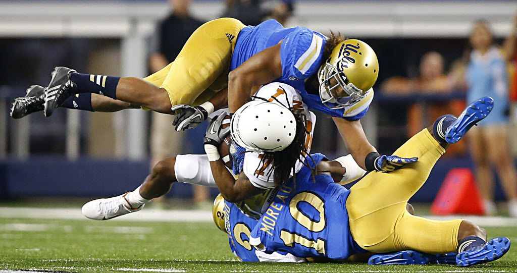 Texas Longhorns wide receiver Marcus Johnson (7) is tackled by UCLA Bruins defensive back Fabian Moreau (10) and linebacker Eric Kendricks (6) in the third quarter  at AT&T Stadium in Arlington, Texas, Saturday, September 13, 2014. (Tom Fox/The Dallas Morning News) 04282015xSPORTS