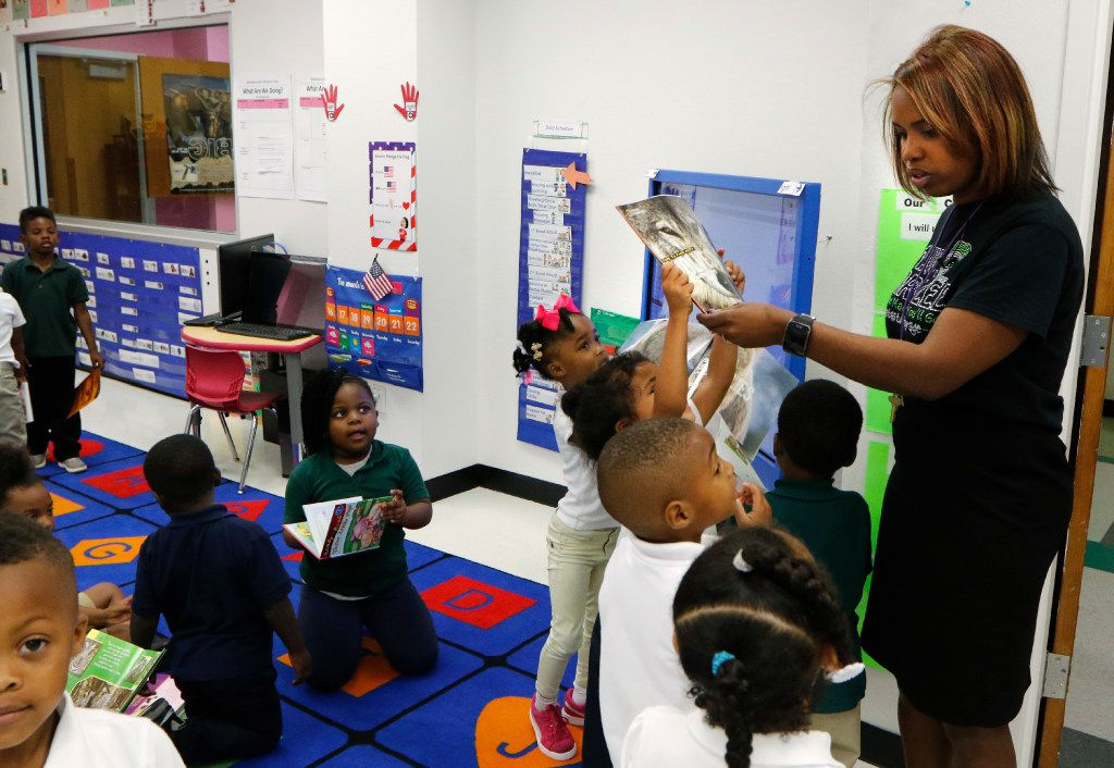 Jisel Johnson (center), 4, holding a book, tries to get the attention of Principal Onjaleke Brown at N.W. Harllee Early Childhood Center in Dallas.