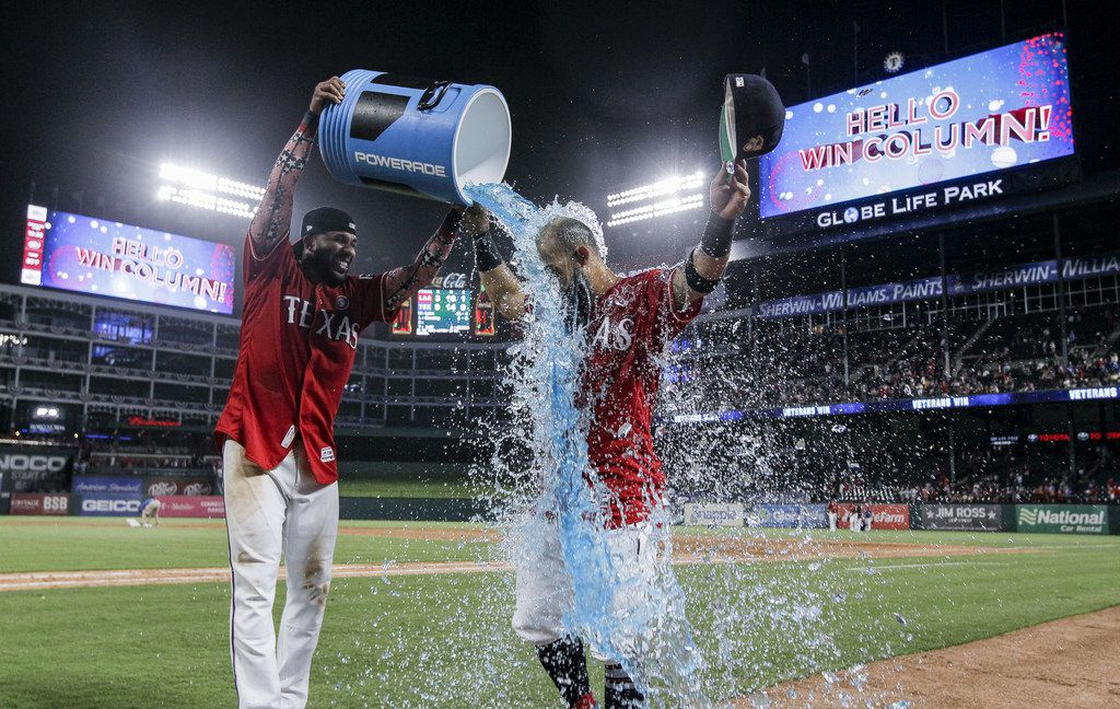 ARLINGTON, TX - JULY 4: Elvis Andrus #1 of the Texas Rangers, left, dumps a cooler of sports drink onto Rougned Odor #12 in celebration of their 9-3 win over the Los Angeles Angels of Anaheim after a baseball game at Globe Life Park in Arlington on July 4, 2019 in Arlington, Texas. Texas won 9-3. (Photo by Brandon Wade/Getty Images)