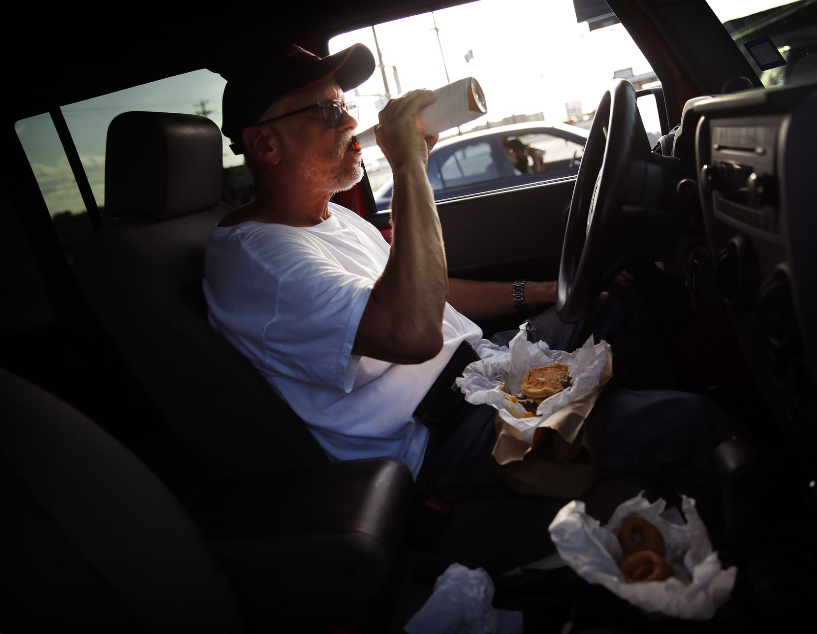Parked in his Jeep, Ray Pena of Dallas enjoys a Miller Lite with a No. 5 double patty burger and onion rings at Keller's Drive-In on Northwest Highway in Dallas, Thursday, May 14, 2020. Ray said he's is a regular, stopping by a couple days a week. (Tom Fox/The Dallas Morning News)