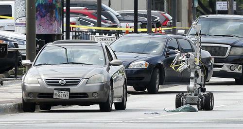 Un robot antibombas se acerca al vehículo del sospechoso de una balacera en el centro de Dallas. TOM FOX/DMN