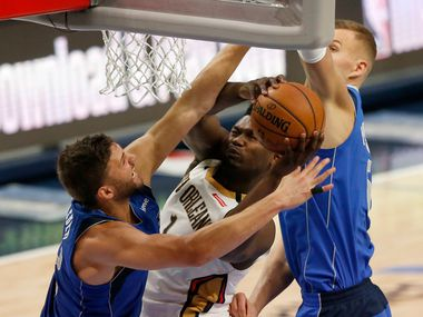New Orleans Pelicans forward Zion Williamson (1) is is fouled as he goes up against Dallas Mavericks forward Maxi Kleber (42) and Dallas Mavericks forward Kristaps Porzingis (6) during the second half of play at American Airlines Center in Dallas on Wednesday, March 4, 2020. Dallas Mavericks defeated the New Orleans Pelicans 127-123.