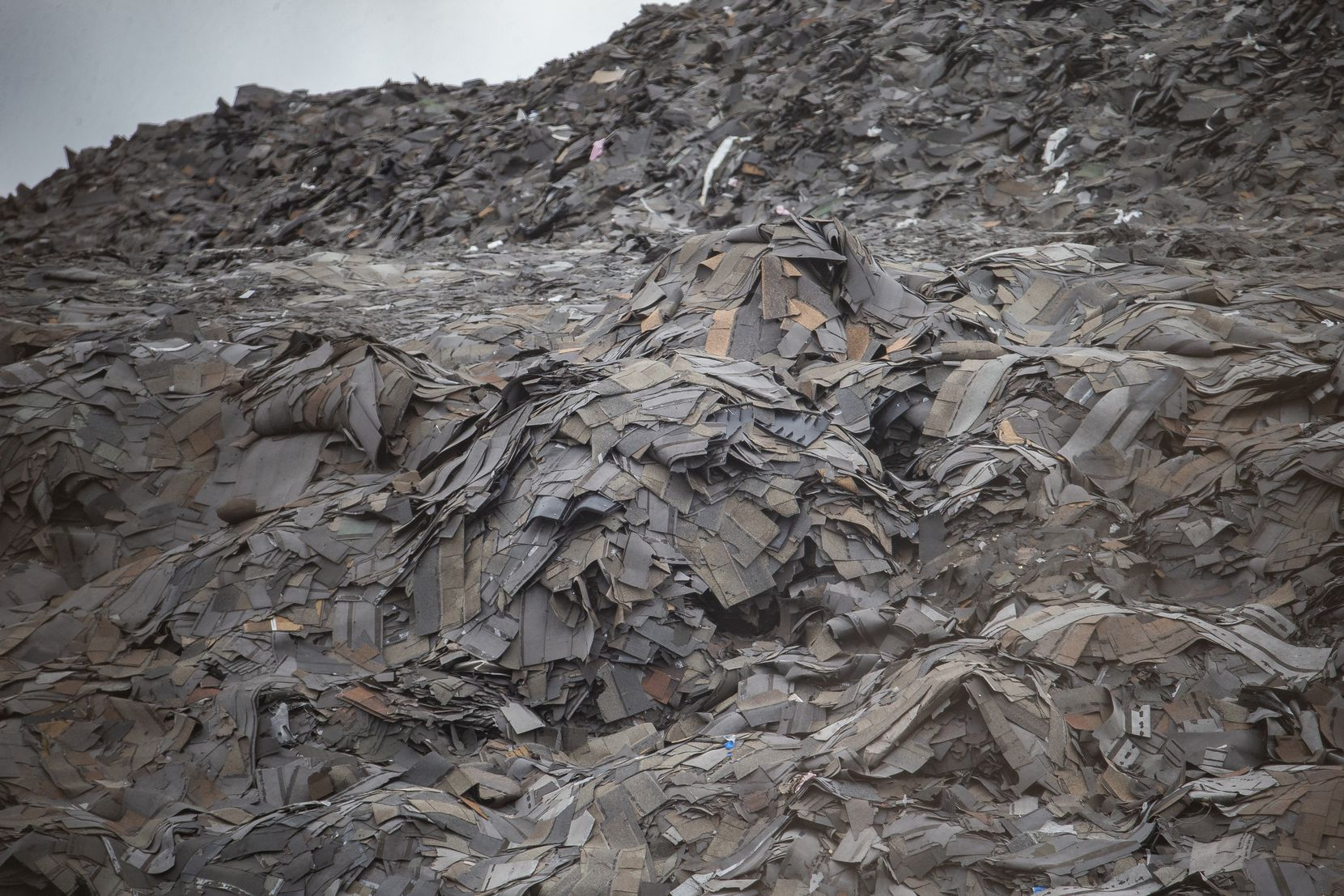 A closeup of the mountain of roofing shingles at what remains of Blue Star Recycling off South Central Expressway in southern Dallas, not too far from Paul Quinn College