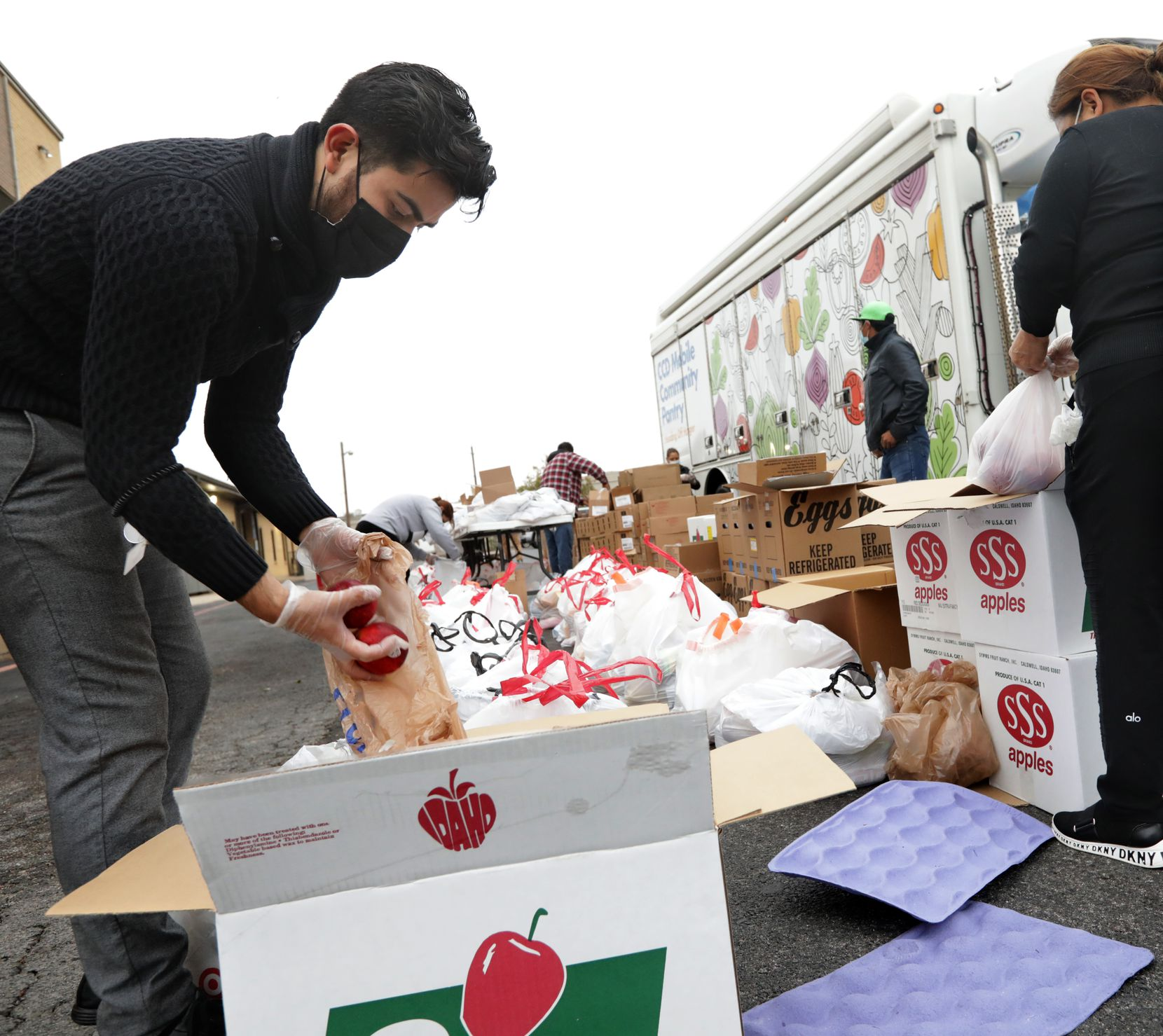 "Margarito ""Jr."" Garcia, left, helps prepare food and essentials bags to distribute to the Texas needy at San Juan Diego Catholic Church in Dallas, TX, on Nov. 24, 2020."
