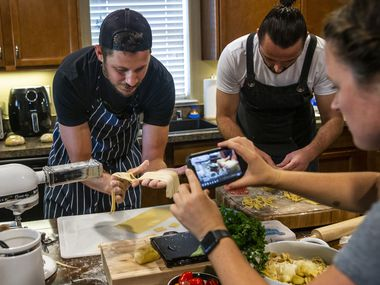 Benchmark Hospitality conference planner Christie Wilson (right) films chef Kyle Wilson (left) and sous-chef Kreshnik Mucllari as they broadcast a cooking lesson to other company employees on Facebook Live from Wilson's home in Fort Worth on Sept. 16.