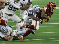 Washington Football Team running back Antonio Gibson (24) is brought down by Dallas Cowboys free safety Xavier Woods (25) during the first quarter of an NFL football game at AT&T Stadium on Thursday, Nov. 26, 2020, in Arlington. (Smiley N. Pool/The Dallas Morning News)