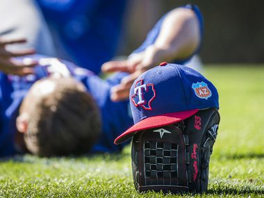 Texas Rangers pitchers stretch after a spring training workout at the team's training facility as a glove and hat ress on the field during on Friday, Feb. 26, 2016, in Surprise, Ariz.