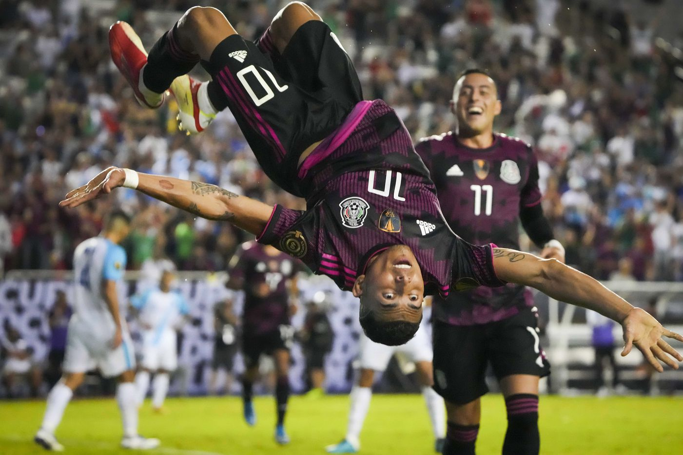 Mexico midfielder Orbelin Pineda celebrates with a flip after scoring past Guatemala goalkeeper Nicholas Hagen as forward Rogelio Funes Mori (11), who scored twice in the game, joins the celebration during the second half of a CONCACAF Gold Cup Group A soccer match at the Cotton Bowl on Wednesday, July 14, 2021, in Dallas.