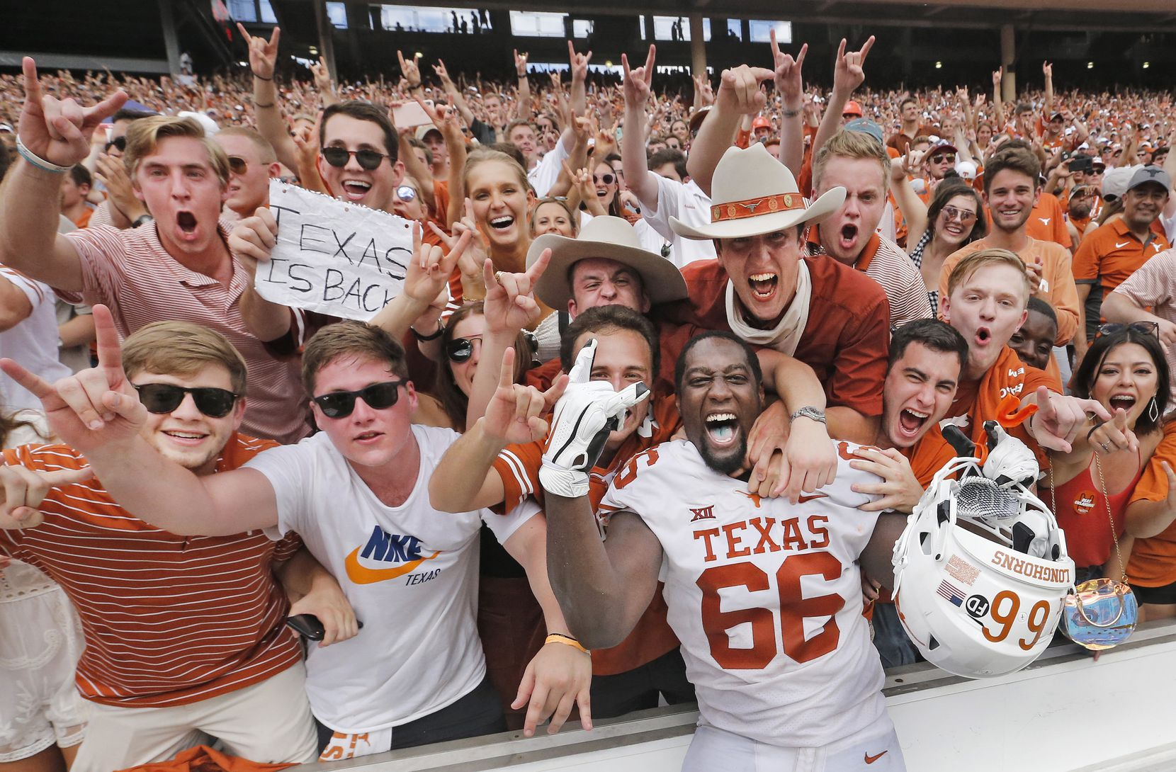 University of Texas offensive lineman Calvin Anderson (66) celebrates with fans during the NCAA football game between the Longhorns and the University of Oklahoma at the Cotton Bowl in Dallas on Saturday, October 6, 2018.