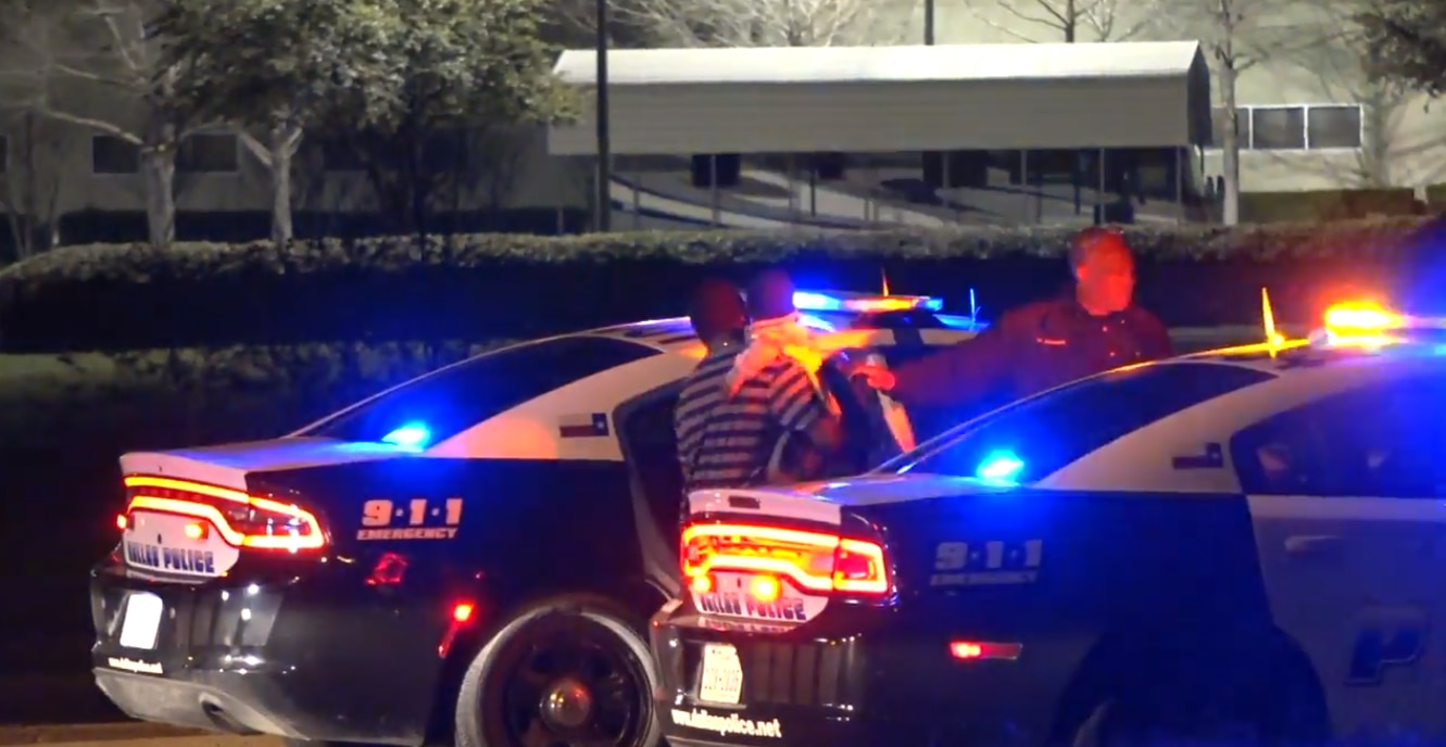 A Red Bird man and his 3-year-old son get inside a police car after an accidental shooting involving the toddler and his brother.