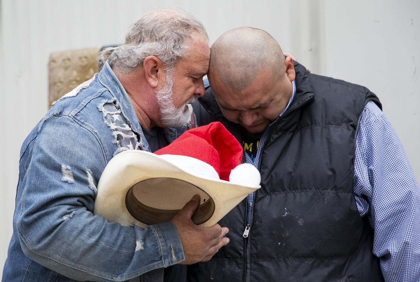 Leon Birdd (left) prayed over local faith leader and volunteer Israel Alonso as he came to load up from the Birdds' food pantry in Mesquite to take back to his community on Dec. 20, 2019.