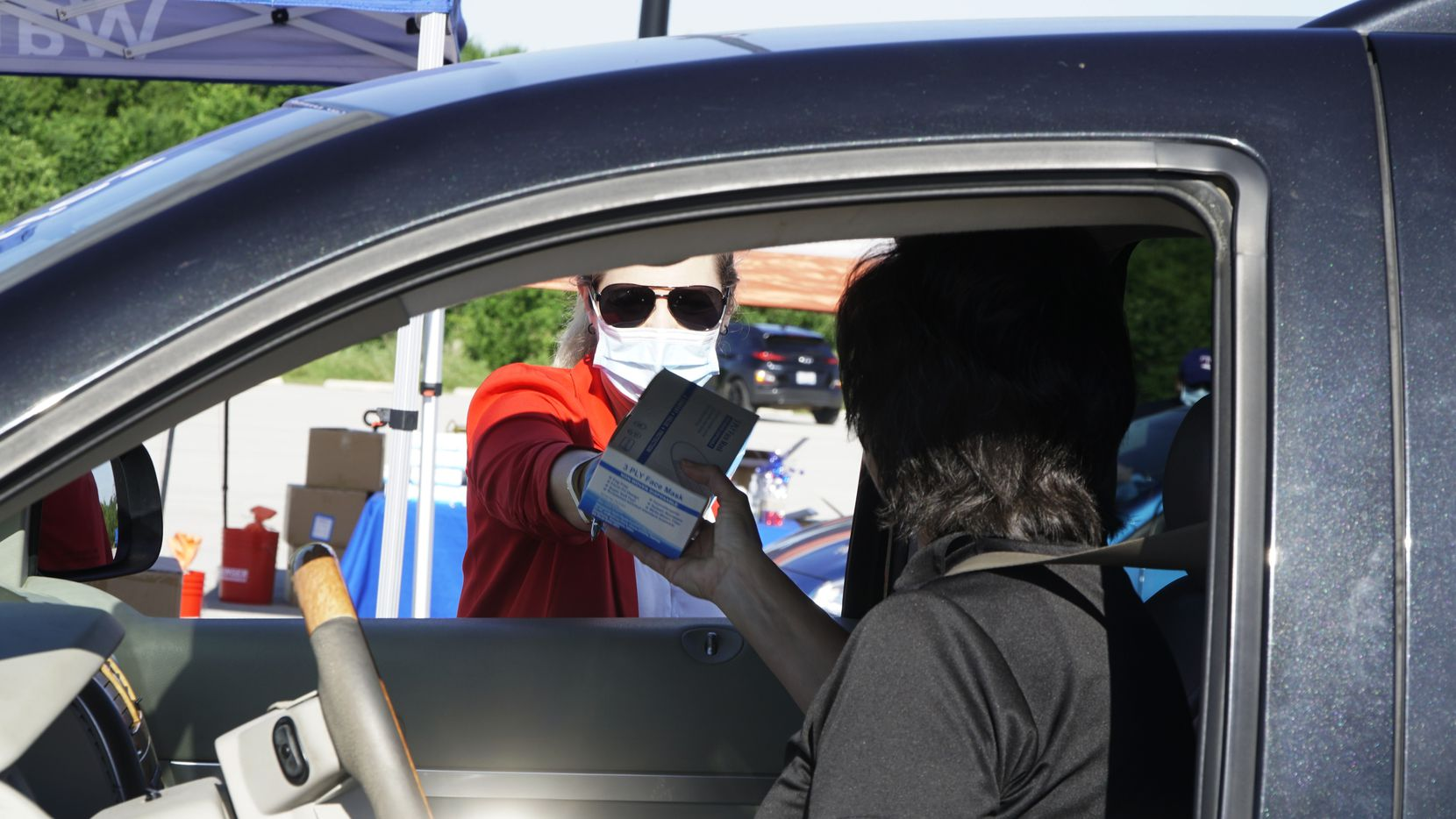 Aimee Rockhill-Carpenter assists someone during a free mask giveaway in the parking lot at Globe Life Park in Arlington, Texas on Wednesday, May 6, 2020. The City of Arlington in partnership with Tarrant County, the Texas Rangers, Greater Arlington Chamber of Commerce, and Arlington Convention and Visitors Bureau provided protective masks for free to employees at Arlington businesses and restaurants.