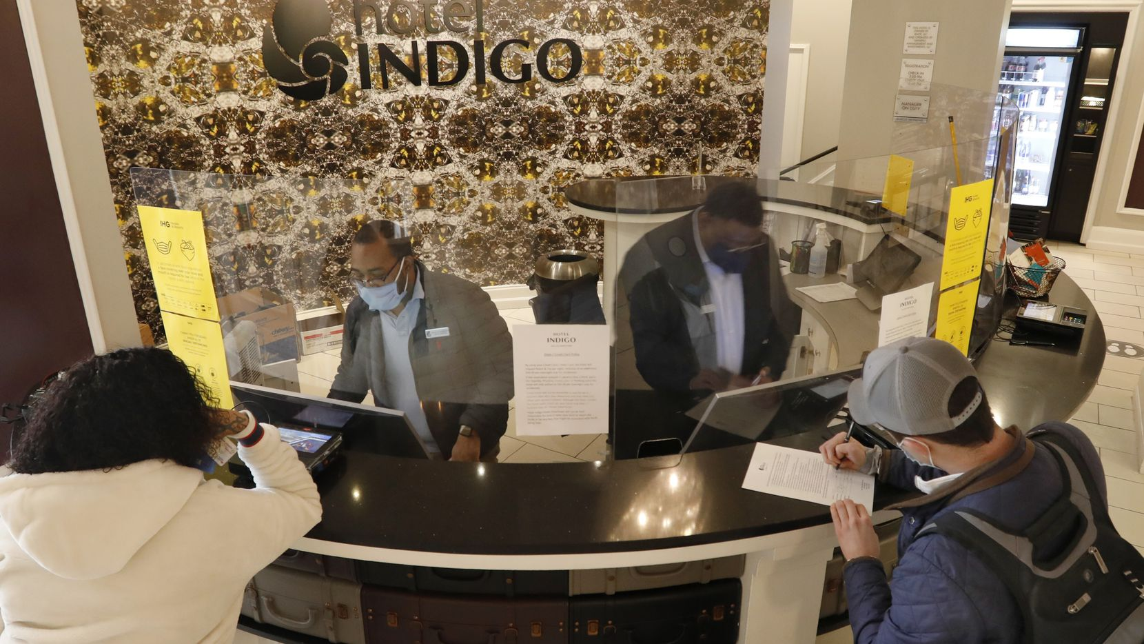General Manager Marcus Hennigan, back left, and Brian Smith, back right, check in guests at Hotel Indigo in Dallas last month. From 2019 to 2029, the number of hotel clerks in the U.S. could decline by 22%, in large part because of the pandemic's lasting effects, according to a recent report by economists at the U.S. Bureau of Labor Statistics.
