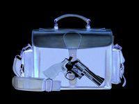 Una imagen de rayos X que muestra a una pistola en una maleta de viaje.