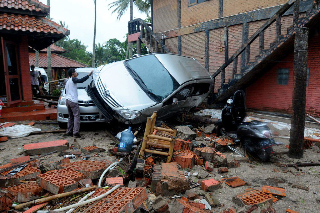 Debris from buildings and damaged cars are seen in Anyer, Serang on December 23, 2018, after the area was hit by a tsunami on December 22 following an eruption of the Anak Krakatoa volcano. - A volcano-triggered tsunami has left at least 222 people dead and hundreds more injured after slamming without warning into beaches around Indonesia's Sunda Strait, officials said on December 23, voicing fears that the toll would rise further. (Photo by Dasril Roszandi / AFP)DASRIL ROSZANDI/AFP/Getty Images