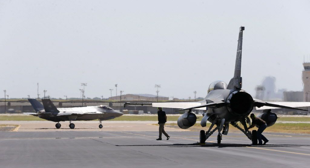 "A crew prepares an F-16 to escort an F-35 for a test flight at Lockheed Martin  in Fort Worth. ""We are in the phase of rapidly accelerating and growing"" the building of F-35s,  a Pentagon executive officer said recently."