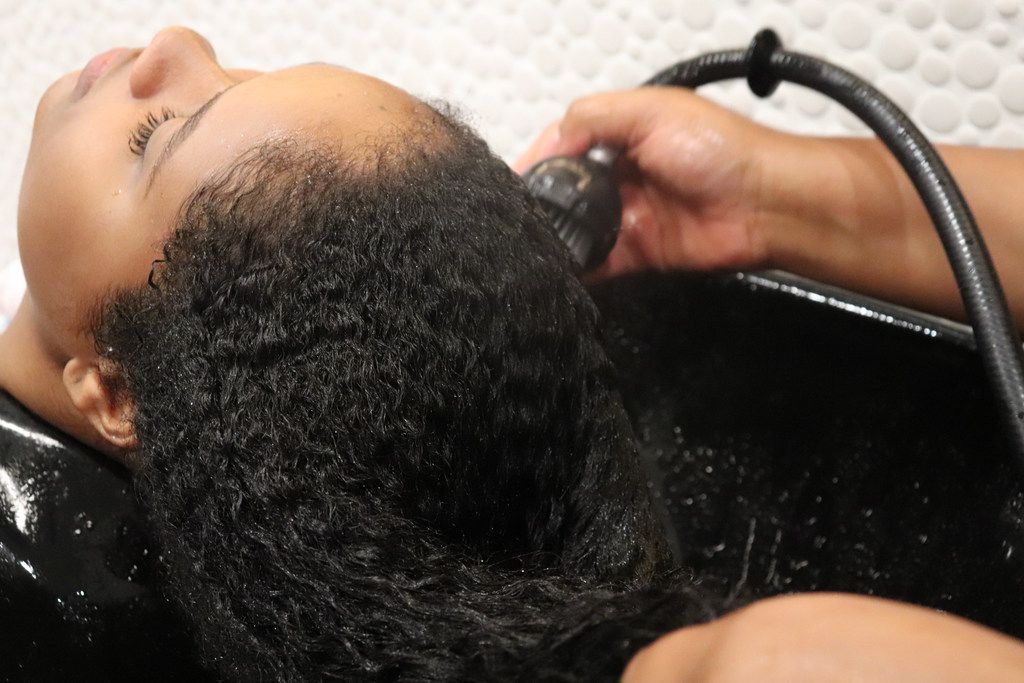 A woman has her hair washed by a Pressed Roots stylist.