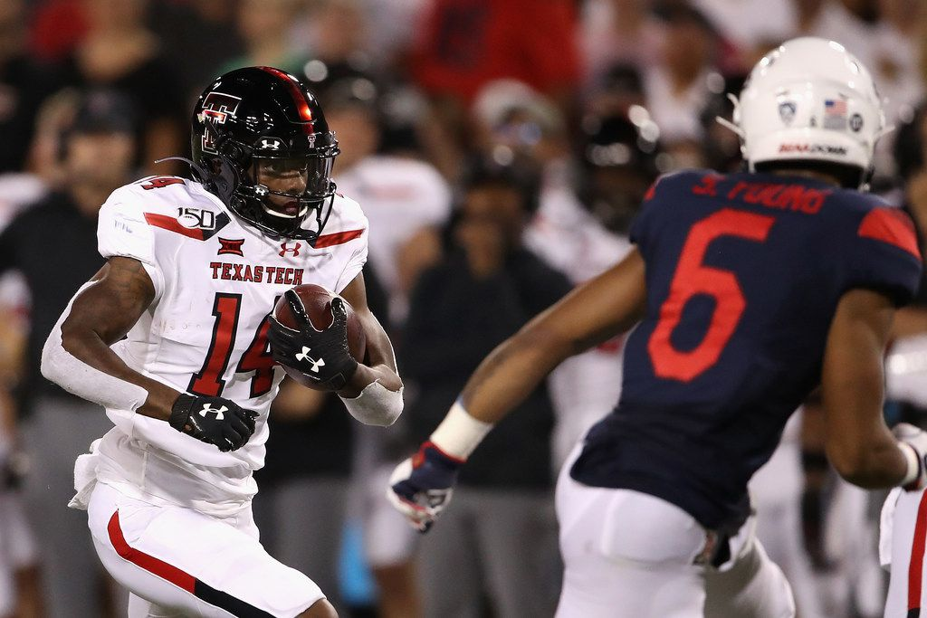 TUCSON, ARIZONA - SEPTEMBER 14:  Wide receiver Xavier White #14 of the Texas Tech Red Raiders runs with the football after a reception against safety Scottie Young Jr. #6 of the Arizona Wildcats during the first half of the NCAAF game at Arizona Stadium on September 14, 2019 in Tucson, Arizona.