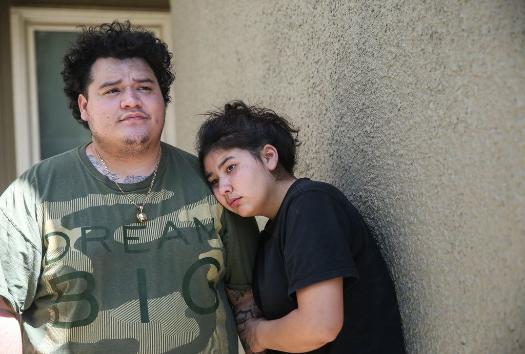Audrey Flores (right) rests her head on the shoulder of her boyfriend, D'Marco Gonzalez, as they watch fire crews work the scene of a 3-alarm apartment fire at 1226 N. Masters Drive on Friday. Flores recently moved into the building that burned to stay with her sister, Ashley Flores.