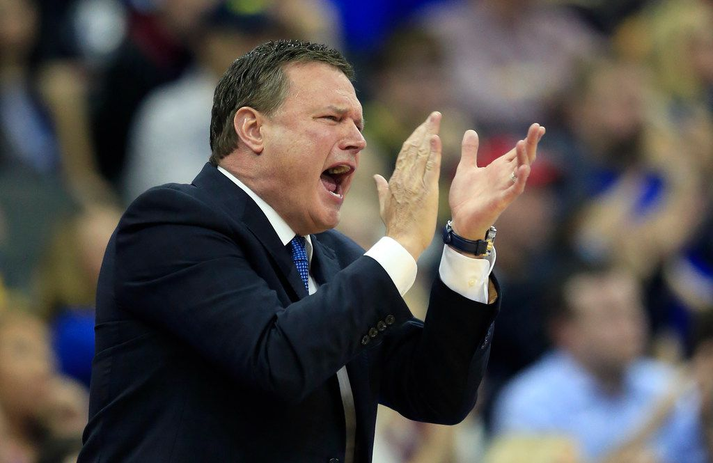 FILE - In this Thursday, March 23, 2017, file photo, Kansas coach Bill Self applauds his team during the first half of a regional semifinal against Purdue in the NCAA men's college basketball tournament, in Kansas City, Mo. Kansas is eyeing its 14th consecutive Big 12 title and another NCAA Tournament run with a new cast of characters during the 2017-18 season. (AP Photo/Orlin Wagner, File)