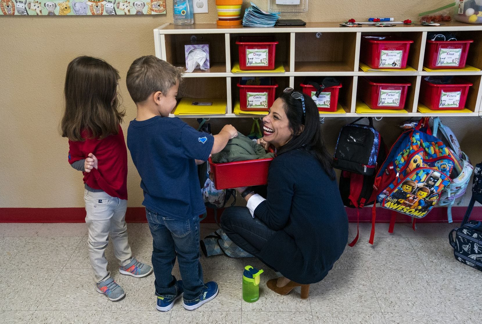 Director Jennifer Granadillo helps Rhys Yanez, 4, find his jacket in a classroom on Nov. 18, 2019, at Spanish Schoolhouse in Coppell. Sofia Morales, 4, is at left. Granadillo is among several Venezuelan teachers at the Spanish-speaking preschool.