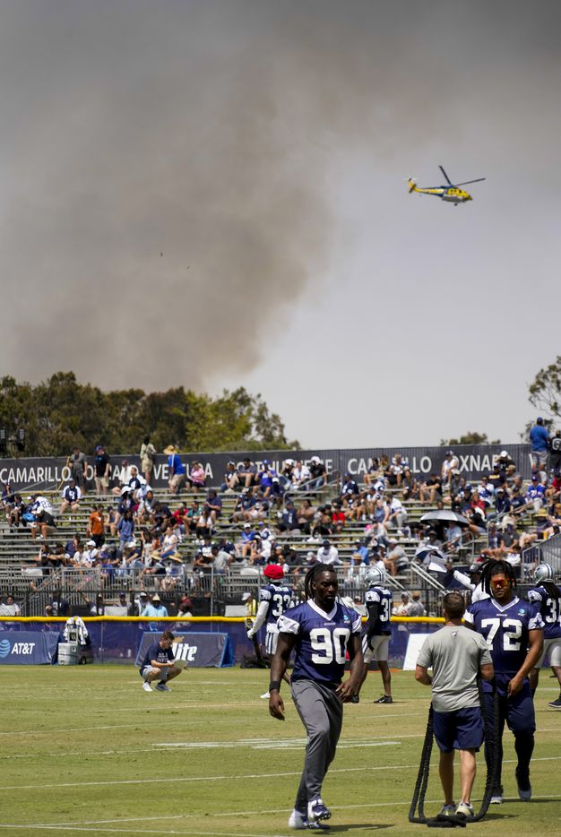 A firefighting helicopter works to control a fire near the facility as the Dallas Cowboys practice at training camp on Wednesday, July 28, 2021, in Oxnard, Calif.