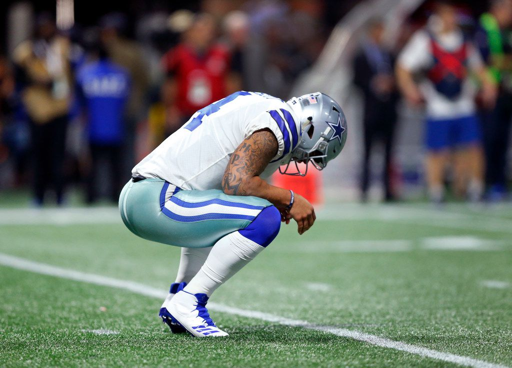 FILE - Cowboys quarterback Dak Prescott (4) stretches his back after taking a hit in the fourth quarter of a game against the Falcons on Sunday, Nov. 12, 2017, at Mercedes-Benz Stadium in Atlanta.