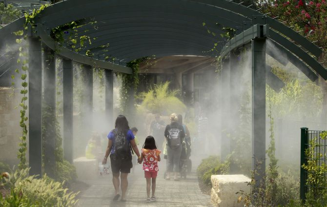 Patrons walk through water misters at the new Rory Meyers Children's Adventure Garden at the The Dallas Arboretum in Dallas, Texas on Friday, August 16, 2013.