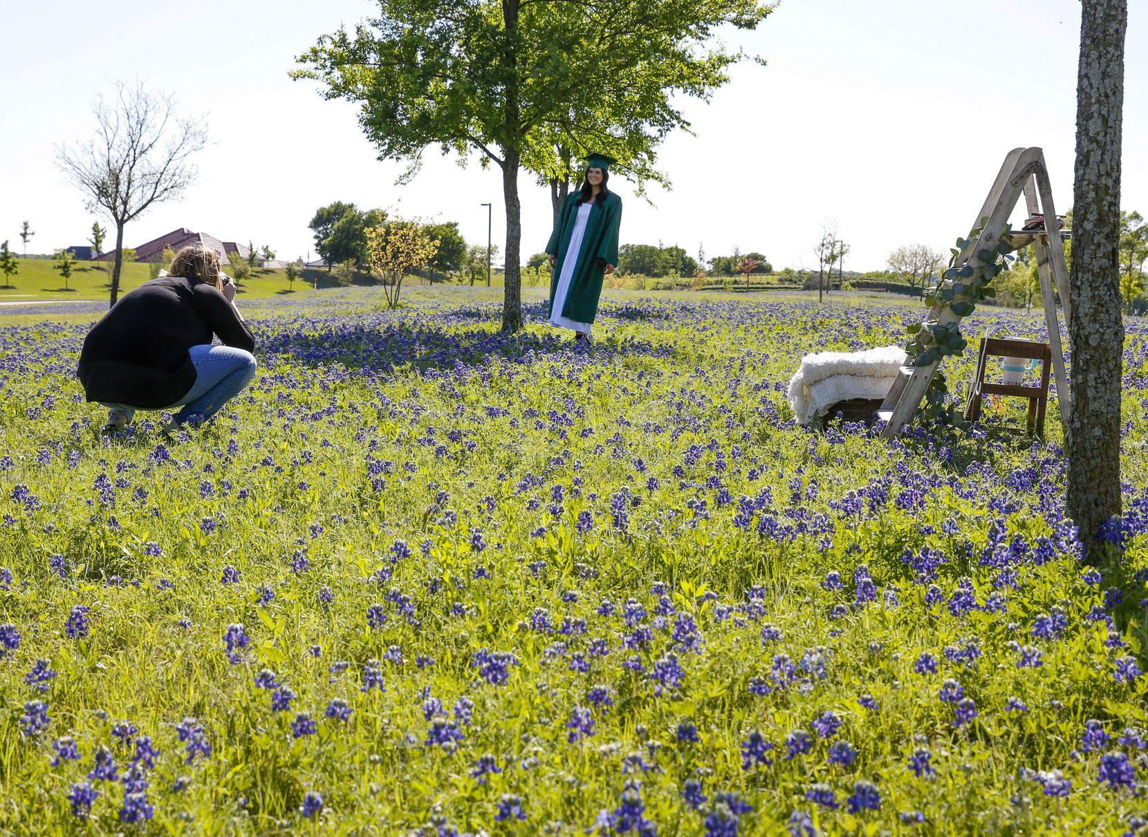 Jenny Burns of jujuB Photography takes senior pictures of Reedy High School (Frisco ISD) student Landry Thompson in a bluebonnet field in a median on W. Bethany Drive in Allen, Texas on April 14, 2019.