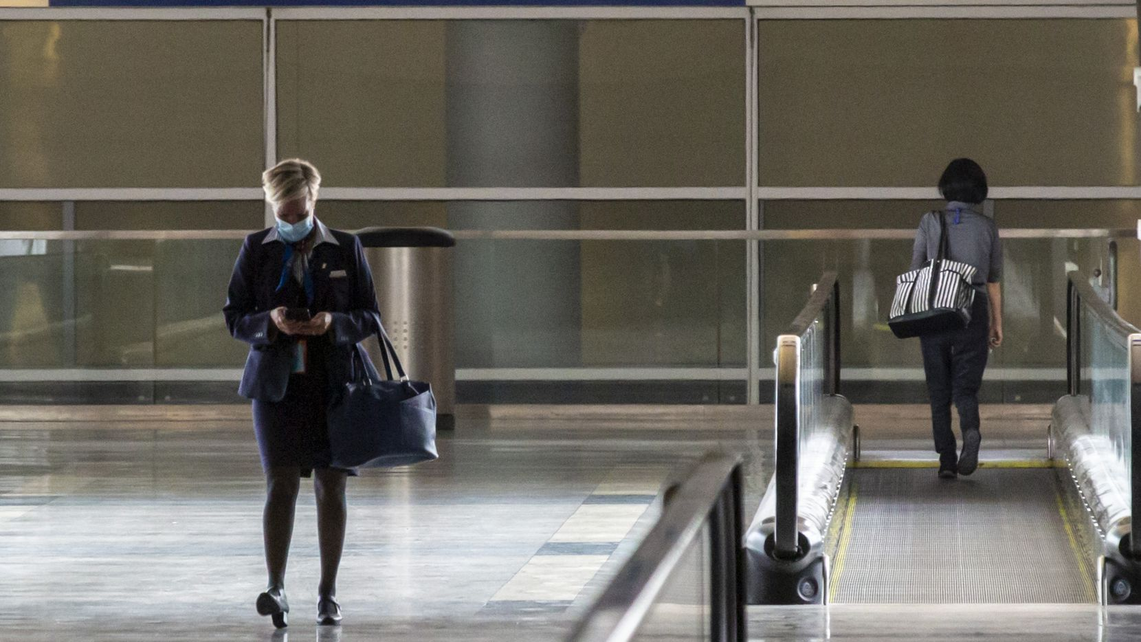 An airlines employee walks out of Terminal D at DFW International Airport in Irving, Texas, on Sunday, July 26, 2020. (Lynda M. Gonzalez/The Dallas Morning News)