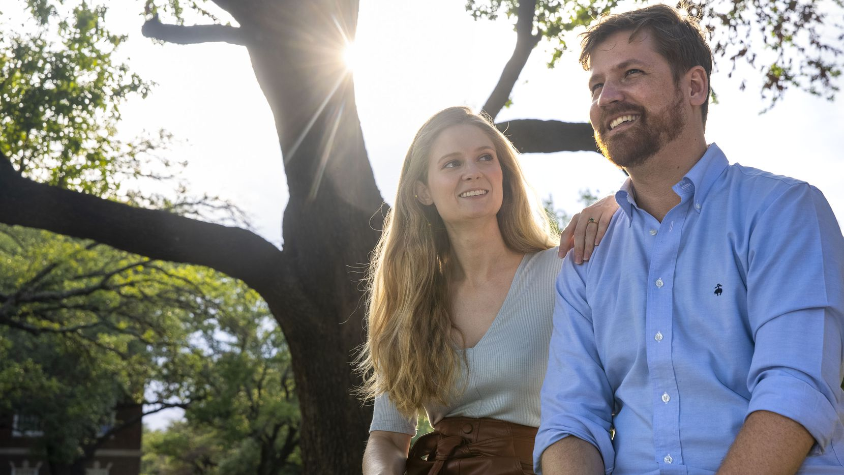 From left, James McCormick and Lauren Ammerman, fiancés and doctors in cell and molecular biology, laugh together during a portrait session on the Southern Methodist University campus in Dallas on Monday, June 21, 2021. The couple met during their doctoral programs while conducting research around a protein that could improve memory loss. (Lynda M. González/The Dallas Morning News)