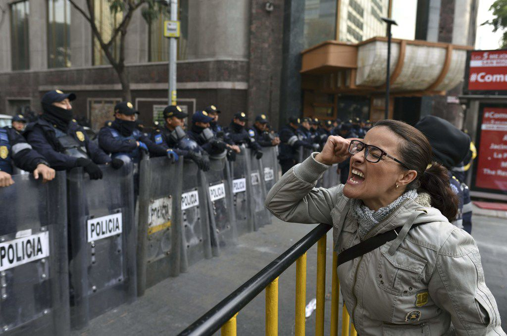 A demonstrator shouts slogans in front of the Senate building in Mexico City during a Dec. 14 protest against the potential approval of an Internal Security Law, which would allow the army to act as police. Mexican deputies approved a new security law that provides a legal framework for military deployment, and the controversial initiative is being discussed in the Senate.