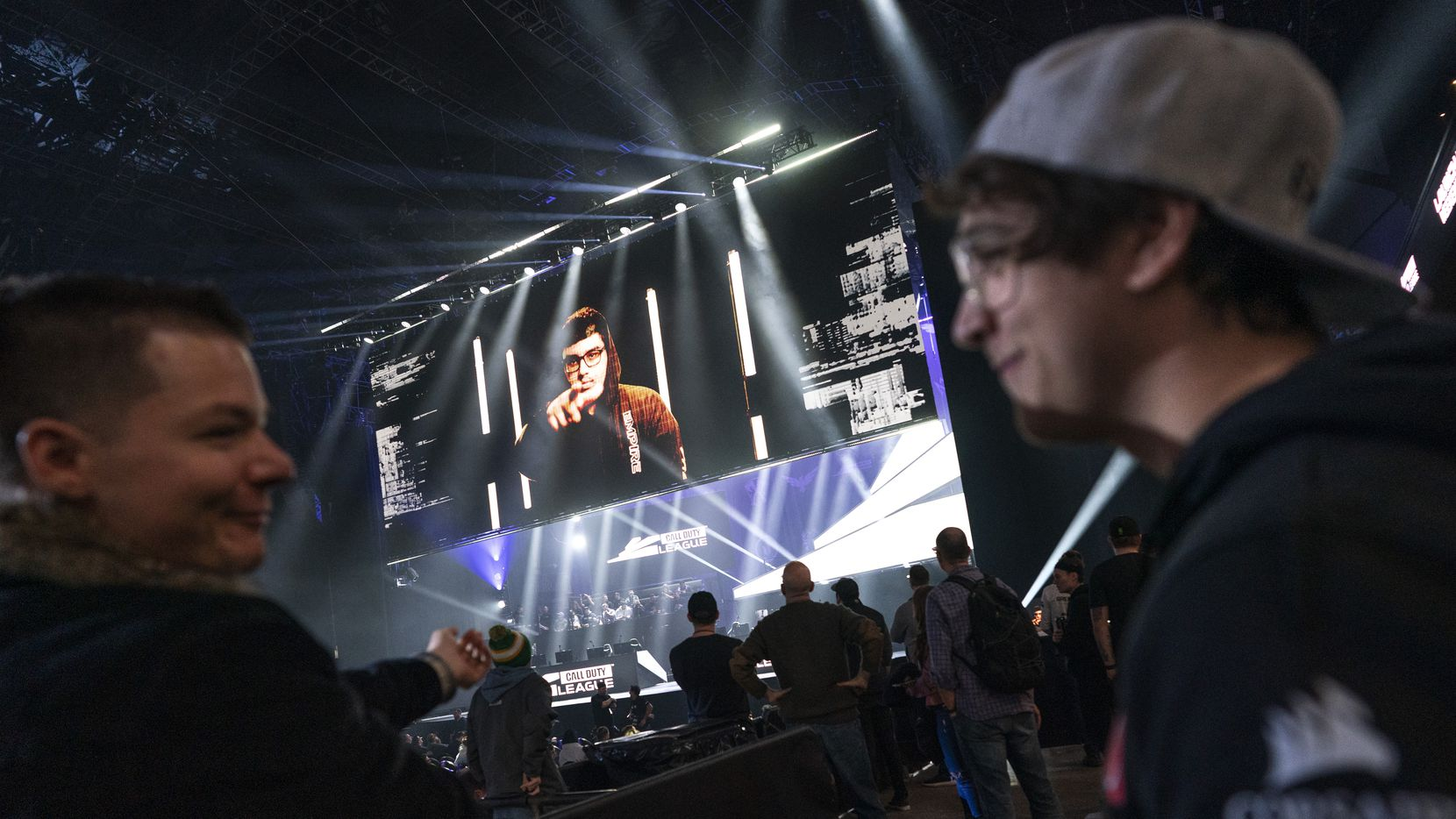 """FILE - James """"Clayster"""" Eubanks (right) chats while Indervir """"iLLeY"""" Dhaliwal appears on screen as his team waits to take the stage for a match between the Dallas Empire and Chicago Huntsmen during CDL Launch Weekend at the Armory in Minneapolis on Jan. 24, 2020."""