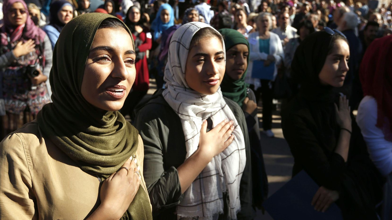 Hiba Loya and Donia Kased both of Houston as the national anthem is sung during a press conference at the steps of the Texas Capitol during the Texas Muslim Capitol Day rally in Austin on Tuesday, January 31, 2017.
