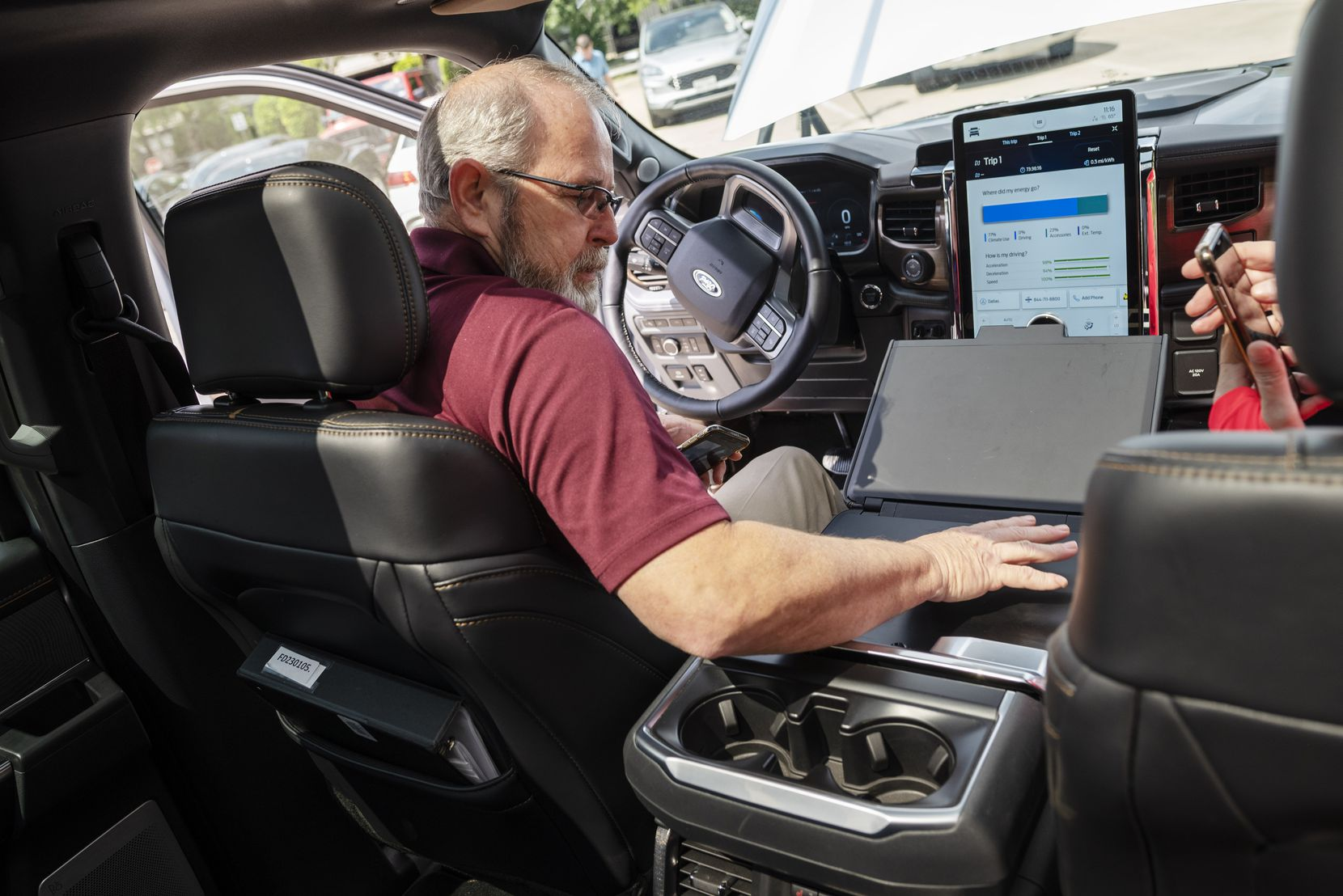 Arthur Grothe, manager of equipment services for the city of Mesquite, tries some of the features, including a folding workstation for using a laptop or writing, inside the Ford F-150 Lightning.