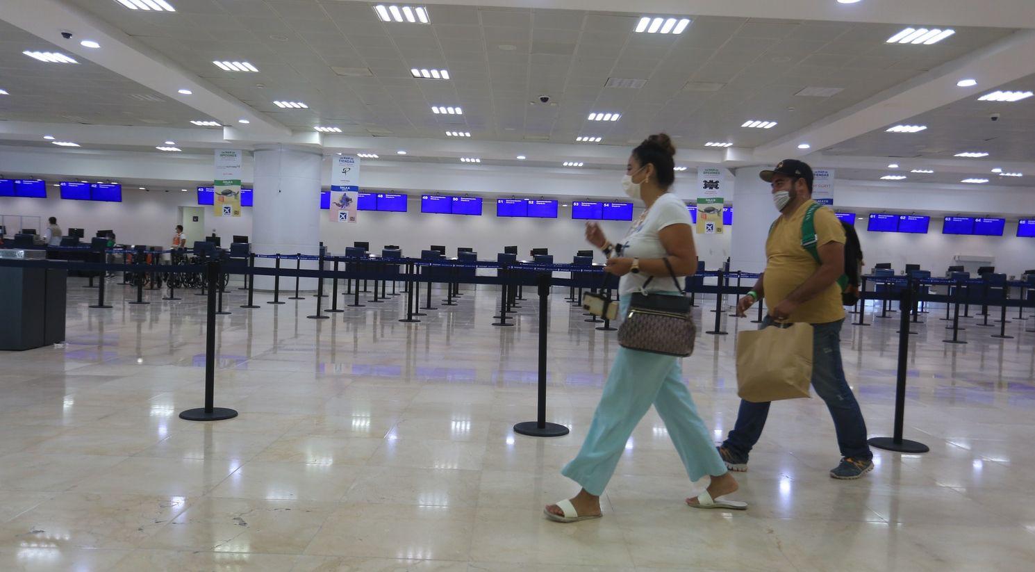 Turistas caminan en la zona de aduanas del aeropuerto internacional de Cancún.