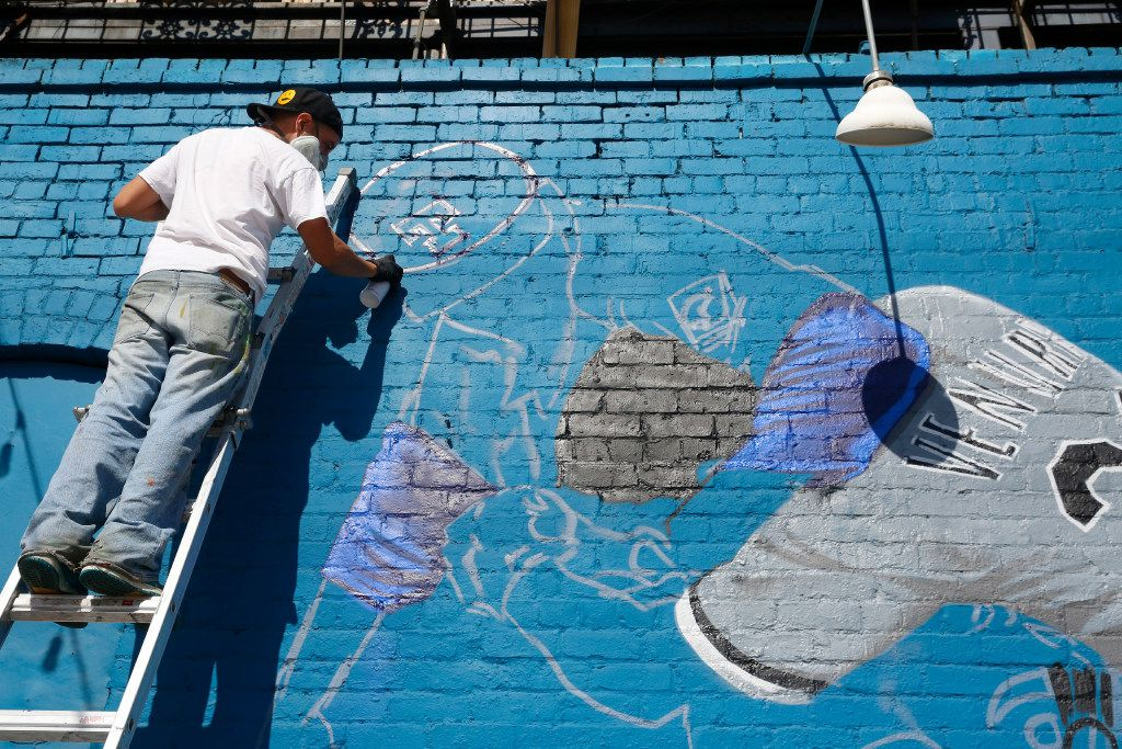 """Dallas-based Muralist Isaac """"IZK"""" Davies paints a mural of the famous Nolan Ryan punch scene on the Crowdus St. side of Wits End in Deep Ellum Tuesday June 06, 2017. This is an early stage of the process. (Ron Baselice/The Dallas Morning News)"""