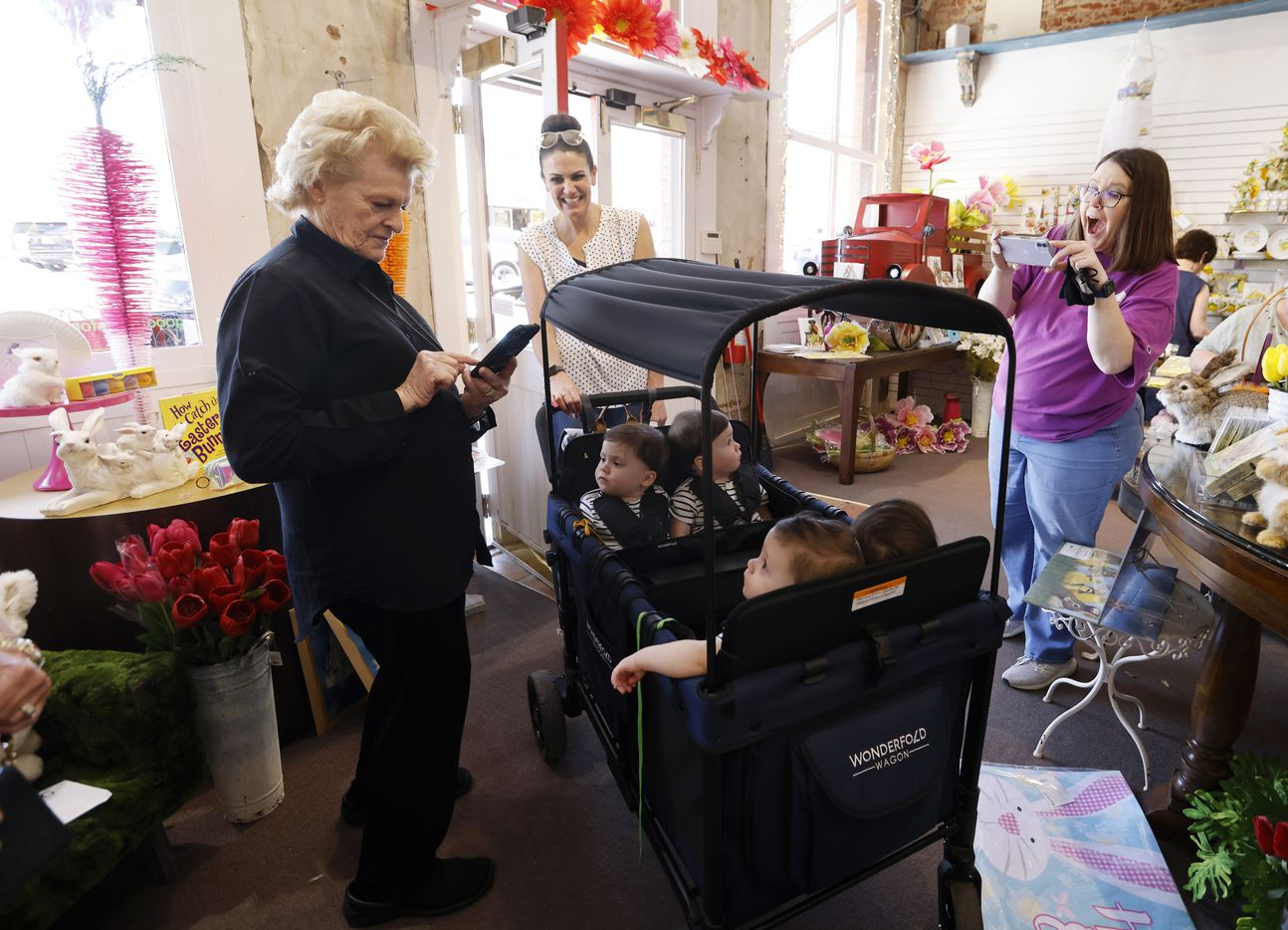 Sally Bultmann (far left), owner of the store Good Things for All Seasons and Leslie Cave (far right) take photos of Harrison Hardy, Henry and Hudson Marr as their mother Jenny Marr looks on inside the store on Friday, March 26, 2021 in Grapevine, Texas.