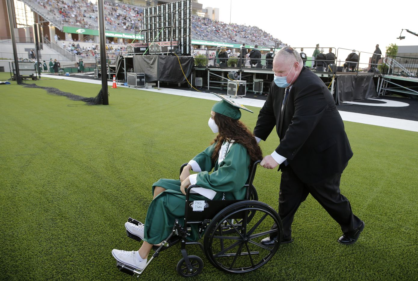Prosper High School softball player Lexie Bell is pushed away from the stage by Prosper softball coach Todd Rainwater after she received her diploma during Prosper High School's graduation ceremony at Children's Health Stadium in Prosper, Texas on Friday, June 5, 2020. Bell signed to play softball at St. Edward's University. But she was recently diagnosed with Ewing Sarcoma, a rare form of cancer.